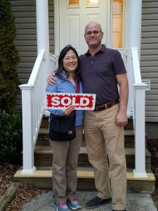 couple standing in front of their new home holding SOLD sign